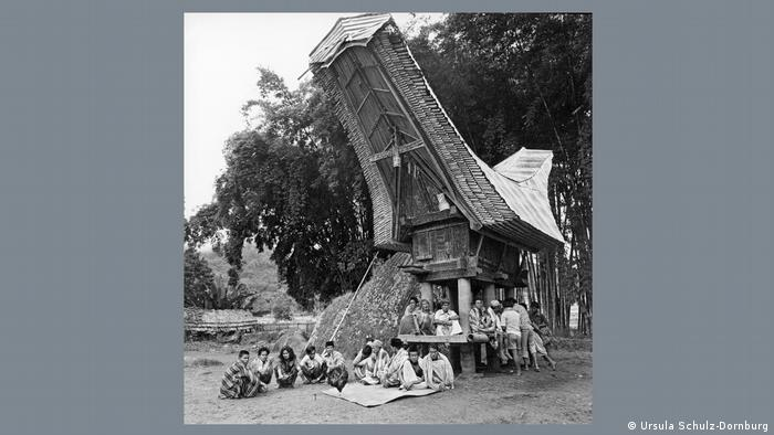 Many people sitting at the base of a lumbung in Indonesia.