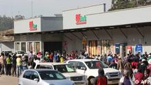 People queue to buy food at a supermarket in Mbabane, Eswatini, on July 1, 2021. - Demonstrations escalated radically in Eswatini this week as protesters took to the streets demanding immediate political reforms. Activists say eight people were killed and dozens injured in clashes with police. Internet access has been limited while shops and banks are shuttered, straining communication and limiting access to basic goods under a dawn-to-dusk curfew. (Photo by - / AFP)