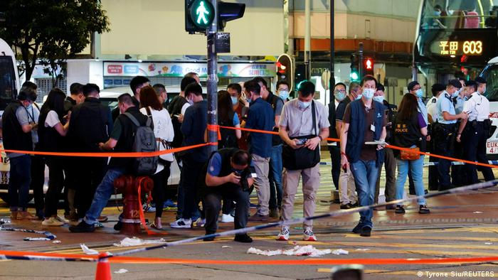 Police take pictures at the site of a knife attack in Hong Kong