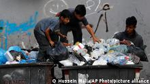 17.06.2021 Boys search garbage containers for valuables and for metal cans that can be resold, in Beirut, Lebanon, Thursday, June 17, 2021. Lebanon has been facing its worst economic crisis in decades, with unemployment figures soaring and the local currency losing more than 90% of its value against the dollar. (AP Photo/Hussein Malla)