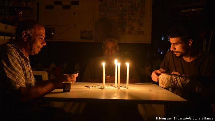 People spend time in the dark during power cuts due to the fuel shortages in Beirut.