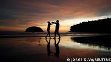 """*** Dieses Bild ist fertig zugeschnitten als Social Media Snack (für Facebook, Twitter, Instagram) im Tableau zu finden: Fach """"Images"""" —> Weltspiegel/Bilder des Tages *** Local residents Stavros from Greece and Valina from Russia dance on an almost empty Kata beach as Phuket reopens to overseas tourists, allowing foreigners fully vaccinated against the coronavirus disease (COVID-19) to visit the resort island without quarantine, in Phuket, Thailand July 1, 2021. REUTERS/Jorge Silva TPX IMAGES OF THE DAY"""