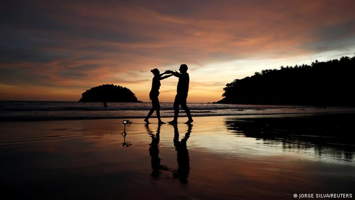 Foreign tourists on an empty beach in Thailand's Phuket province