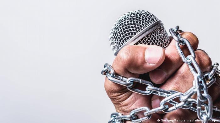 Foto simbólica de una mano,con un micrófono, rodeada de cadenas