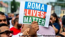 People hold a banner Roma Lives Matter during a rally to honor a Roma man Stanislav Tomas who died after police officers held him in Teplice, Czech Republic, Saturday,June 26, 2021. Tomas died after a police officer responding to a call about an altercation knelt on his neck. Police said the preliminary investigation showed no link between the police intervention and the man's death. But the angry participants condemned the police. (Ondrej Hajek/CTK via AP)
