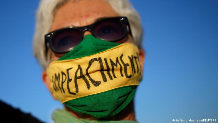 Mulher com faixa verde e amarela com a palavra impeachment