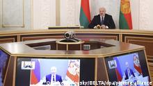 Alexander Lukaschenko, Präsident von Belarus, nimmt an einem Videogespräch mit dem russischen Präsidenten Putin (r, Bildschirm), und russischen und belarussischen Delegierten teil. +++ dpa-Bildfunk +++