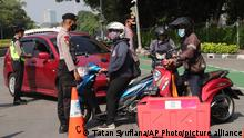Police officers ask motorists to turn around at a check point during the imposition of an emergency restriction to curb the spread of coronavirus outbreak in Jakarta, Indonesia, Saturday, July 3, 2021. Indonesian government announced its strictest measures this year as it battles an explosion of COVID-19 cases that have strained hospitals in the fourth most populous country. (AP Photo/Tatan Syuflana)