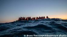 ARCHIV - 12.02.2021, ---: Migranten aus verschiedenen afrikanischen Nationen warten in einem Boot auf Helfer der spanischen NGOOpen Arms, die sich ihnen 122 Meilen vor der libyschen Küste im Mittelmeer nähern. (zu dpa Friedensappelle ungehört: 2020 mehr Menschen denn je auf der Flucht) Foto: Bruno Thevenin/AP/dpa +++ dpa-Bildfunk +++