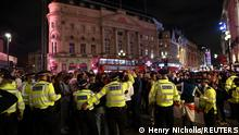 Soccer Football - Euro 2020 - Fans gather in London ahead of Ukraine v England - London, Britain - July 3, 2021 Police officers stand guard as England fans celebrate after the match REUTERS/Henry Nicholls