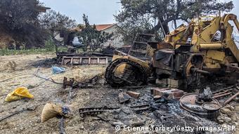 Ora köyü yakınlarında alevlerde zarar gören bir iş makinesi.