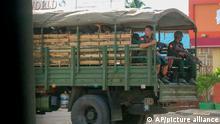 Militärische Truppen und Polizisten patrouillieren in einem Fahrzeug durch eine Stadt. (zu dpa ««Menschenrechtskatastrophe»: UN warnen vor Eskalation in Myanmar») +++ dpa-Bildfunk +++