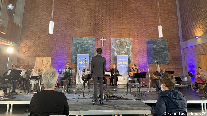 Musikerinnen und Musiker sitzen mit ihren Instrumenten auf einer Bühne, der Dirigent steht mit dem Rücken zum Publikum.