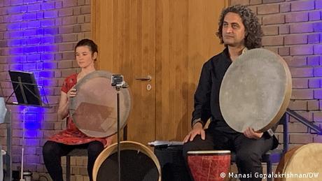 Eine Musikerin und ein Musiker sitzen mit persischen Rahmentrommeln auf einer Bühne.