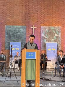 Saman Haddad steht an einem Pult auf einer Bühne und hält eine Rede. Hinter ihm sitzen Musiker.