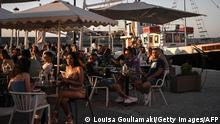 People sit at a cafe-bar in the old town of Chania (La Canee) on the island of Crete on May 14, 2021. - Greece kickstarts its tourism season on May 14, 2021, with both the government and travel operators hoping the lure of sun, sand and sea will bring a sorely needed revenue boost after last year's miserable holiday season amid the covid-19 pandemic. (Photo by Louisa GOULIAMAKI / AFP) (Photo by LOUISA GOULIAMAKI/AFP via Getty Images)