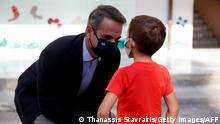 Greece's Prime Minister Kyriakos Mitsotakis speaks with a pupil at a primary school on the first day of class of the new academic year in Athens, on September 14, 2020, amid the crisis linked with the covid-19 pandemic caused by the novel coronavirus. - Schools open on Monday amid concerns due to a new spike in coronavirus infections and along with resistance by some parents to a regulation stipulating that all children and adults must wear protective face masks. (Photo by Thanassis Stavrakis / POOL / AFP) (Photo by THANASSIS STAVRAKIS/POOL/AFP via Getty Images)