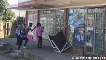 People take pictures of a damaged shop in Mbabane, Eswatini, on June 29, 2021. - Demonstrations escalated radically in Eswatini this week as protesters took to the streets demanding immediate political reforms. Activists say eight people were killed and dozens injured in clashes with police. Internet access has been limited while shops and banks are shuttered, straining communication and limiting access to basic goods under a dawn-to-dusk curfew. (Photo by - / AFP) (Photo by -/AFP via Getty Images)