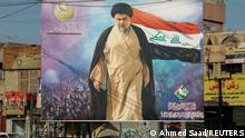 A poster of Iraqi Shi'ite cleric Moqtada al-Sadr in the Sadr City district of Baghdad, Iraq June 21, 2021. The text at the top left of the poster reads 'The Solid Structure'. The text at the bottom right of the poster reads 'Saraya al-Salam, operation command of holy Samarra'. Picture taken June 21, 2021. To match Special Report IRAQ-CLERIC/ REUTERS/Ahmed Saad