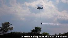 """A helicopter flies over the burned Larnaca mountain region near Ora village, Cyprus, Sunday, July 4, 2021. Cyprus' interior minister says four people have died in what he called the """"most destructive fire in the island nation's history. (AP Photo/Petros Karadjias)"""