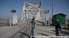 In this photograph taken on March 20, 2016, Afghan border police personnel stand guard on the Afghan side of the AfghanistanUzbekistan bridge in Hairatan. Hairatan, the only crossing between Afghanistan and Uzbekistan, is an ominous bellwether of economic activity in northern Afghanistan. It is here, and at four other entry points on the borders with Tajikistan and Turkmenistan, that construction materials, flour and household products are exported from Central Asia to Afghanistan. / AFP / FARSHAD USYAN / TO GO WITH Afghanistan-unrest-economy,FEATURE by Guillaume Decamme (Photo credit should read FARSHAD USYAN/AFP via Getty Images)
