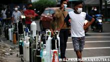 People wearing protective masks queue to refill oxygen tanks as Indonesia experiences an oxygen supply shortage amid a surge of coronavirus disease (COVID-19) cases, at a filling station in Jakarta, Indonesia, July 5, 2021. REUTERS/Willy Kurniawan