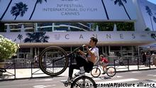 A member of the public rides a bicycle whilst passing the Palais des during preparations for the 74th international film festival, Cannes, southern France, July 5, 2021. The Cannes film festival runs from July 6 - July 17. (AP Photo/ Brynn Anderson)