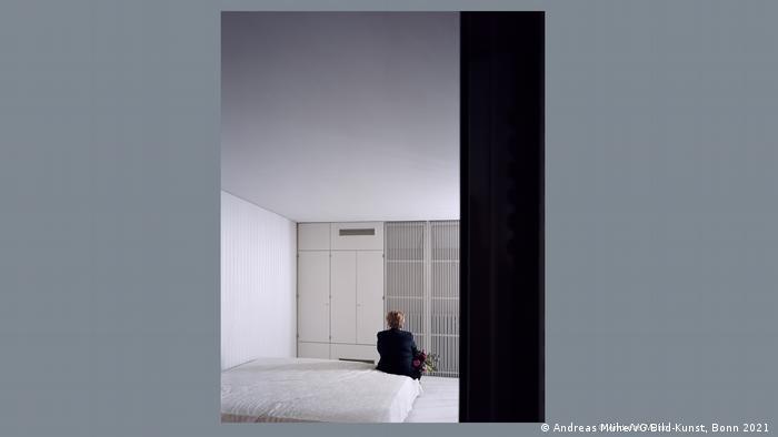 Wanita yang sosoknya seperti Angela Merkel duduk di kamar tidur memunggungi kamera.