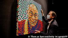 French auctioneer Arnaud Oliveux adjusts the mosaic Rubik Dalai Lama by French street artist Invader on a wall during its presentation before it goes under the hammer next July 5, at the Artcurial auction house in Paris on June 2, 2021. - - RESTRICTED TO EDITORIAL USE - MANDATORY MENTION OF THE ARTIST UPON PUBLICATION - TO ILLUSTRATE THE EVENT AS SPECIFIED IN THE CAPTION (Photo by Thomas SAMSON / AFP) / RESTRICTED TO EDITORIAL USE - MANDATORY MENTION OF THE ARTIST UPON PUBLICATION - TO ILLUSTRATE THE EVENT AS SPECIFIED IN THE CAPTION / RESTRICTED TO EDITORIAL USE - MANDATORY MENTION OF THE ARTIST UPON PUBLICATION - TO ILLUSTRATE THE EVENT AS SPECIFIED IN THE CAPTION (Photo by THOMAS SAMSON/AFP via Getty Images)