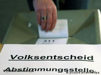 A voter puts her ballot paper in the box in the Hamburg referendum
