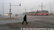A woman crosses a street, early in the morning, amid the smog covering Sofia on November 27, 2020. - Winter smog season has settled in and Bulgaria's soaring coronavirus death rate, one of Europe's highest, is prompting experts to warn about a compound health risk from air pollution and Covid-19. (Photo by NIKOLAY DOYCHINOV / AFP) (Photo by NIKOLAY DOYCHINOV/AFP via Getty Images)
