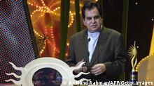 SINGAPORE, SINGAPORE: Indian veteran actor Dilip Kumar awarded oustanding achievement in Indian cinema at the 5th International Indian Film Academy (IIFA) Awards in Singapore 22 May 2004. New York-set love story Kal Ho Naa Ho (Tomorrow May Not Be There) scooped the International Indian Film Academy Awards on Saturday as Singapore was treated to a Bollywood extravaganza of passion and energy. AFP PHOTO/ROSLAN RAHMAN (Photo credit should read ROSLAN RAHMAN/AFP via Getty Images)