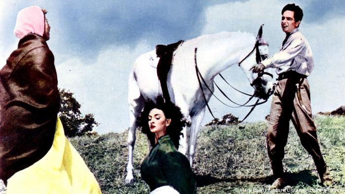 Filmstill: Dilip Kumar hält ein Pferd, zwei Frauen sind im Film AAN - AAN neben ihm