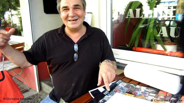 Armagan Isbay with artworks in front of him in his pizzeria