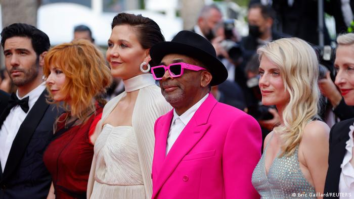 Man in pink suit and glass stands with two women on either side