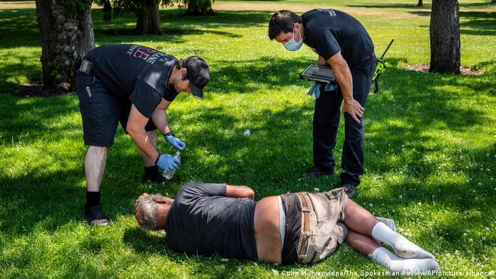 Ein Mann liegt am Boden in einem Park, Polizisten versorgen ihn mit Wasser