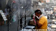 A man stands by fans spraying air mixed with water vapour deployed by donors to cool down pedestrians along a street in Iraq's capital Baghdad on June 30, 2021 amidst a severe heat wave. (Photo by AHMAD AL-RUBAYE / AFP) (Photo by AHMAD AL-RUBAYE/AFP via Getty Images)