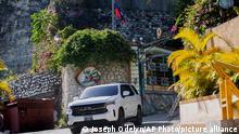 Ein Fahrzeug fährt aus der Einfahrt der Residenz von Moïse, fotografiert durch eine Windschutzscheibe. Der haitianische Präsident ist in der Nacht in seiner Residenz überfallen und tödlich verletzt worden. Seine Ehefrau sei bei dem Angriff verletzt worden, teilte die Regierung des Karibikstaats mit. +++ dpa-Bildfunk +++