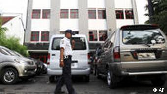 A security guard walks outside the office of Tempo magazine in Jakarta.