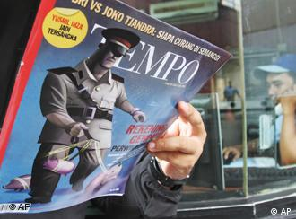 A man reads the latest edition of Tempo magazine featuring a story on police corruption in Jakarta