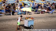 A granita seller walks past people sitting on sun loungers and under sunshades at the beach in Ostia on the outskirts of Rome, on July 22, 2017. / AFP PHOTO / FILIPPO MONTEFORTE (Photo credit should read FILIPPO MONTEFORTE/AFP via Getty Images)