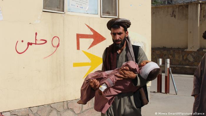 مردی در حال انتقال کودکی که در جنگ در شهر قلعه نو زخمی شده است