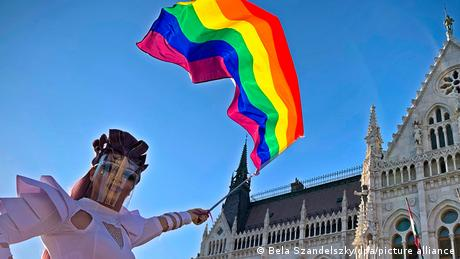 Person wearing face shield holding rainbow flag against blue sky, buuilding in background