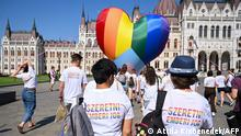 Activists wear shirts reading Love is a human right as they fly a giant heart balloon in rainbow colors during a flashmob in order to protest against a new law in front of the parliament in Budapest on July 8, 2021. - A Hungarian anti-paedophilia bill that came into force on July 8, 2021 was condemned as homophobic by civil organisations during the protest. The law banning the display or promotion of homosexuality or gender change to minors has sparked widespread outcry and threats of sanctions from Brussels if the bill is not rectified. (Photo by ATTILA KISBENEDEK / AFP)