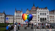 TOPSHOT - Activists fly a giant heart balloon in rainbow colors as they perform a flashmob in order to protest against a new law in front of the parliament in Budapest on July 8, 2021. - A Hungarian anti-paedophilia bill that came into force on July 8, 2021 was condemned as homophobic by civil organisations during the protest. The law banning the display or promotion of homosexuality or gender change to minors has sparked widespread outcry and threats of sanctions from Brussels if the bill is not rectified. (Photo by ATTILA KISBENEDEK / AFP)