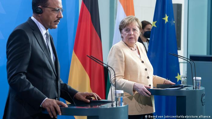 Niger's Mohamed Bazou and Angela Merkel stand together