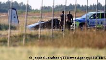 Police officers observe a small aircraft that crashed at Orebro Airport, Orebro, Sweden, July 8 2021. TT News Agency/Jeppe Gustafsson via REUTERS ATTENTION EDITORS - THIS IMAGE WAS PROVIDED BY A THIRD PARTY. SWEDEN OUT. NO COMMERCIAL OR EDITORIAL SALES IN SWEDEN.