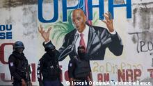Police stand near a mural featuring Haitian President Jovenel Moise, near the leader's residence where he was killed by gunmen in the early morning hours in Port-au-Prince, Haiti, Wednesday, July 7, 2021. (AP Photo/Joseph Odelyn)