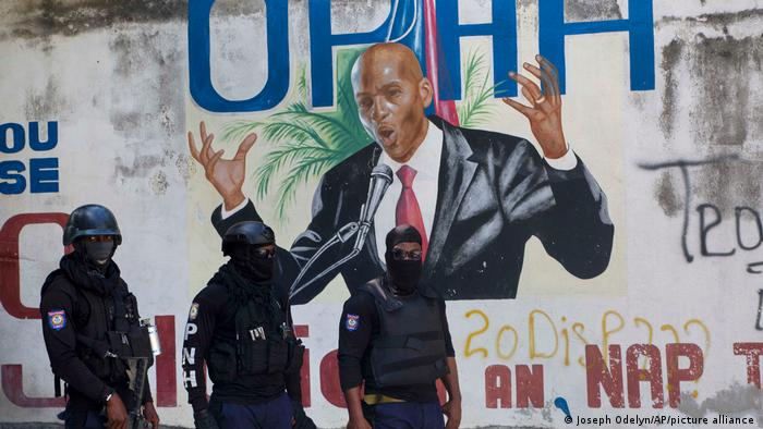 Police waking past a mural depicting Jovenel Moise