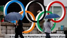Passanten gehen an einer Statue mit übergroßen OlympischenRinge vorbei. Während der Olympischen Spiele wird in Tokio erneut der Corona-Notstand herrschen. Der Notstand soll von kommendem Montag bis vorläufig zum 22. August gelten. Die Olympischen Spiele 2020 Tokio finden vom 23.07.2021 bis zum 08.08.2021 statt. +++ dpa-Bildfunk +++